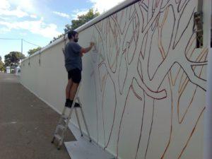 Pintando árboles en la paredes del Pabellón Infantil